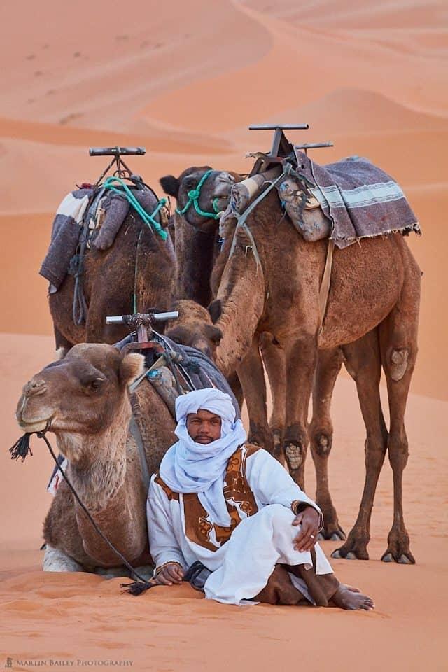 Camel Handler Sitting with Camels